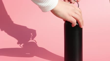 reutilizável : Female hands close a metal reusable bottle for water on a pink background Stock Footage