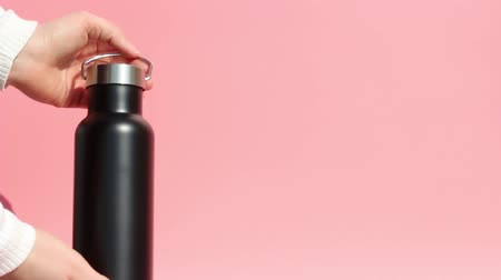 reutilizável : Female hands are holding a reusable metal bottle for water on pink background. Stock Footage