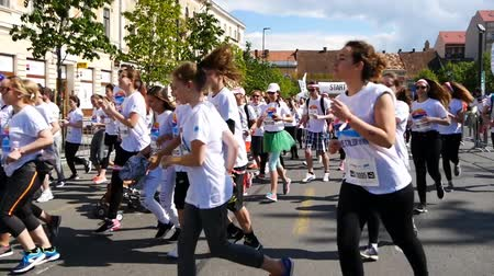 kilometer : CLUJ-NAPOCA, ROMANIA - May 14, 2017: Color Run participants of all ages and genders wearing colorful t-shirts and headbands take off from the starting line as the race begins. Stock Footage