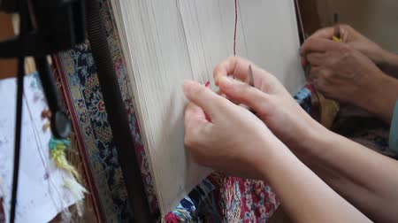orientale : Silk carpet with hand woven. Two women are weaving silk carpet by hand Stock Footage