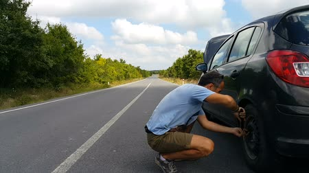 emergency stop : Explosion A man, car tire replacement. Tire changing on countryside