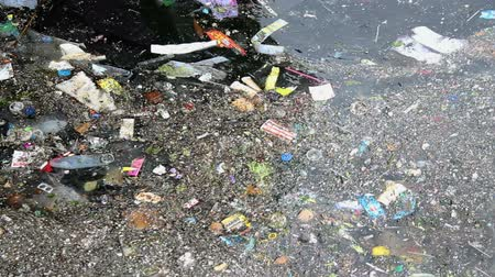 Sea water pollution. Environmental pollution. Garbage on the sea. Rippling garbage accumulated over the sea