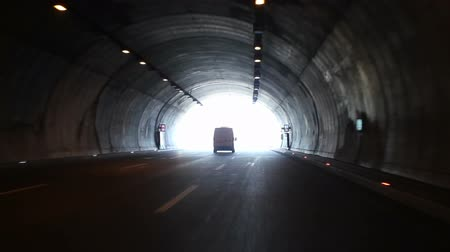 drive through : Vehicle exits through dark highway tunnel