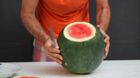 Man in orange shirt is cutting watermelon with chef knife. Black background Stock Footage