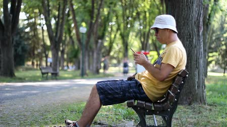 Man in hat and sunglasses using smartphone in park on the bench. Man using smartphone while relaxing in the park