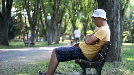 Man in hat and sunglasses is sleeping in park on the bench. Man resting and sleeping in park on bench under trees a summer day. Man napping in the park Stock Footage
