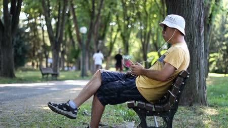 Man in hat and sunglasses sitting on bench in park. Man listens to music with phone while relaxing in the park under trees a summer day
