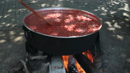 Traditional making tomato paste in boiler with wood fire in the village