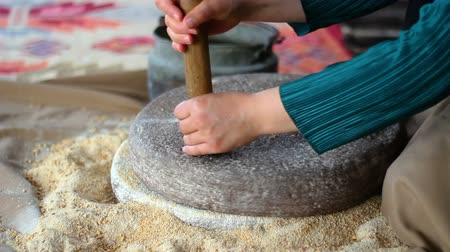 grit : Woman is grinding wheat by hand in stone mill Stock Footage