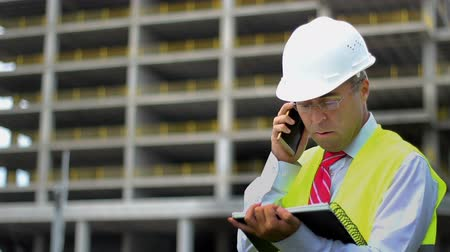 Construction engineer man in shirt and tie with safety helmet and vest works at construction site, talking phone. Concept of people working in industrial field