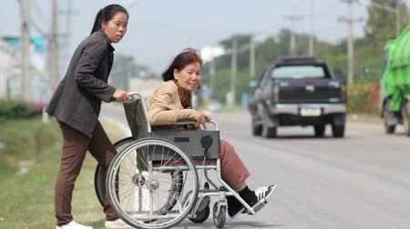rokkant : senior woman using a wheelchair cross street