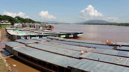 the mekong : Row of Laos and Chinese cargo boats anchored in Mekong river at Chians Sean dock ,Chiangrai ,Thailand.