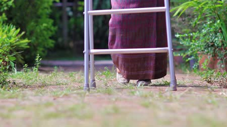 тростник : Elderly woman using a walker at home.
