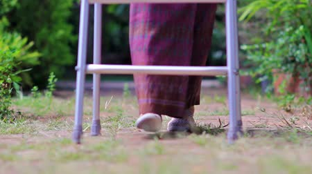 invalidita : Elderly woman using a walker at home.