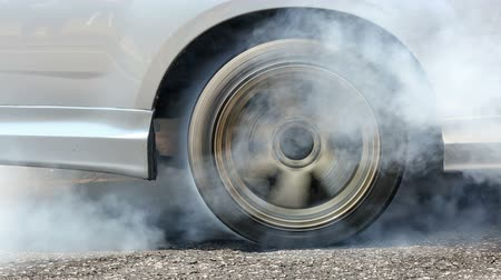 pneus : Drag racing car burns rubber off its tires in preparation for the race Stock Footage