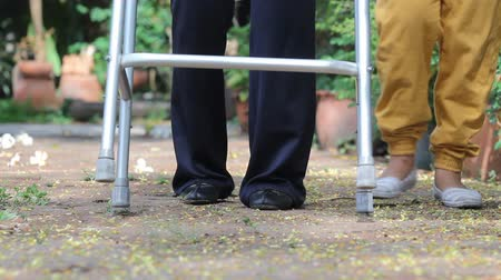 idősek : senior woman using a walker with caregiver in park. (dolly left)