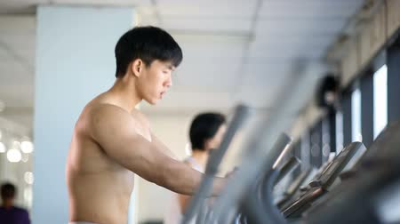 elliptical : Asian man exercise on elliptical trainer machine Stock Footage