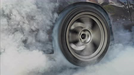 yanmak : Drag racing car burns rubber off its tires in preparation for the race Stok Video