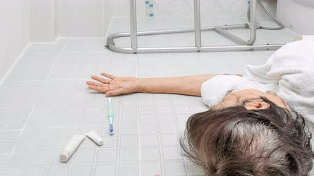 escorregadio : Elderly woman falling in bathroom because slippery surfaces Stock Footage