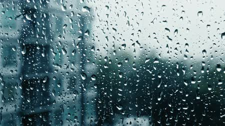 camsı : Drops of rain on a window pane, buildings in background.