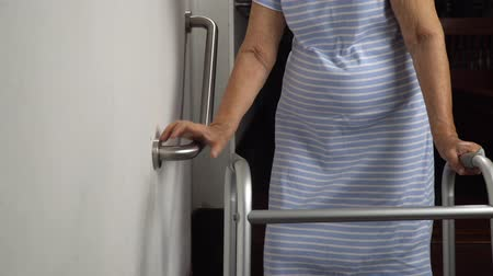 markolat : Elderly woman holding on handrail for safety walk steps