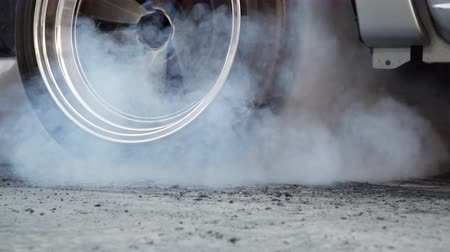 handheld shot : Drag racing car burns rubber off its tires in preparation for the race Stock Footage