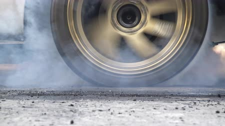 miglio : Drag racing car burns rubber off its tires in preparation for the race Filmati Stock