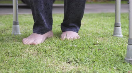 sérülés : Elderly woman walking barefoot therapy on grass in backyard. Stock mozgókép