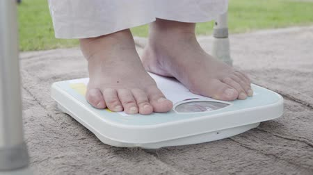 weighing machine : Eldely female standing on weight scale , her weight measure  54 kg.