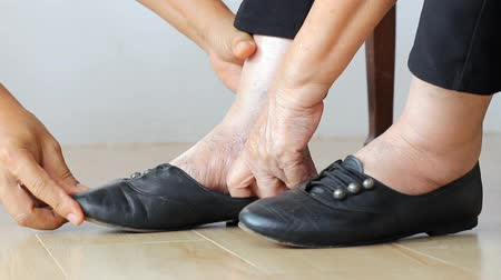 kotník : Elderly woman swollen feet putting on shoes with care giver. Dostupné videozáznamy