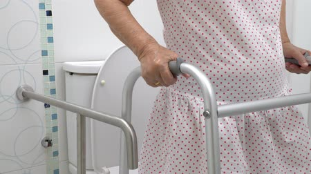 handrails : Elderly woman holding on walker in toilet. Stock Footage