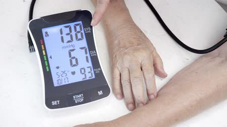 nadciśnienie : Daughter checking blood pressure (hypertension) of elderly mother at home Wideo