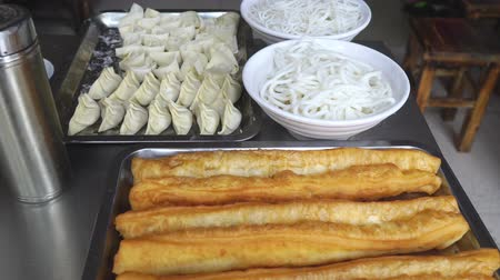 Common breakfast foods in China , deep-fried dough sticks(youtiao),Rice noodles and dumplings on tray prepared for cooking