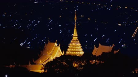 Pagoda in Wat Phra That Doi Suthep at night with lighting of Chiang Mai city background , Thailand .