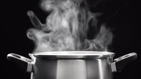 steam over cooking pot in kitchen on dark background Stock Footage