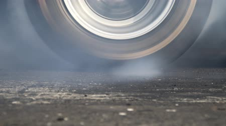 Drag racing car burns rubber off its tires in preparation for the race Stock Footage