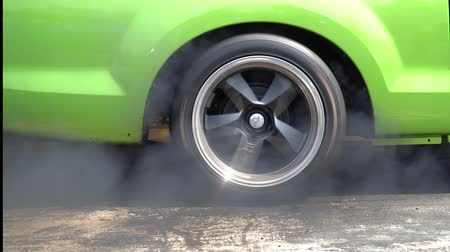 Drag racing car burns rubber off its tires in preparation for the race Wideo