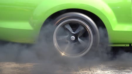 Drag racing car burns rubber off its tires in preparation for the race Archivo de Video