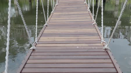 walking on pedestrian suspension bridge Stock Footage