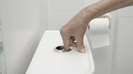 Elderly woman hand flushing toilet Stock Footage