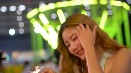 firecrackers : Young Asian woman holding Firecrackers and smiling at night. Stock Footage
