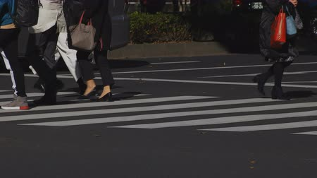crossing road : Walking people body parts at the crossing in the business town in Shinjuku Tokyo