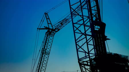 em desenvolvimento : A time lapse of moving cranes behind the blue sky at the under construction dusk