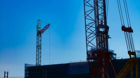 строительные леса : A time lapse of moving cranes behind the blue sky at the under construction dusk