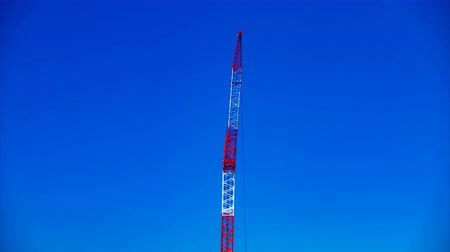 строительные леса : A time lapse of moving cranes behind the blue sky at the under construction daytime