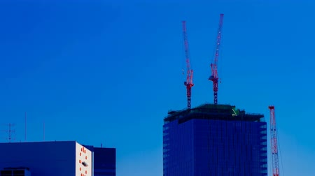 строительные леса : A time lapse of moving cranes on the top of building behind the blue sky in Tokyo