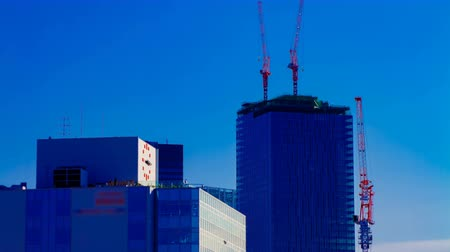 em desenvolvimento : A time lapse of moving cranes on the top of building behind the blue sky in Tokyo
