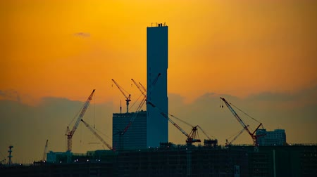 строительные леса : A time lapse of moving cranes at the under construction in Tokyo at dusk tilt Стоковые видеозаписи