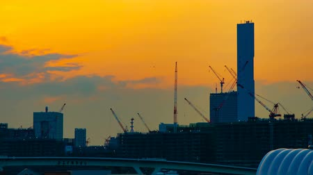 high rises : A time lapse of moving cranes at the under construction in Tokyo at dusk wide shot panning
