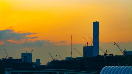 site : A time lapse of moving cranes at the under construction in Tokyo at dusk wide shot tilt
